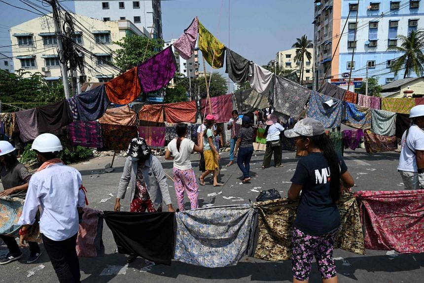 The wraparound cloths, known as longyi, are hung on washing lines.
