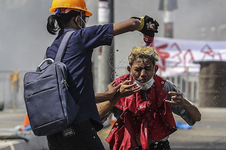 A protester receives a soda wash after being exposed to tear gas fired by police during a protest in Yangon on March 6, 2021.