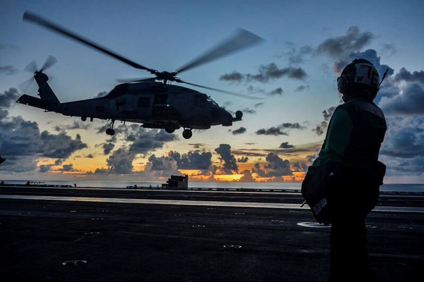 An MH-60R Sea Hawk helicopter launches aboard USS Ronald Reagan in the South China Sea on July 17, 2020.