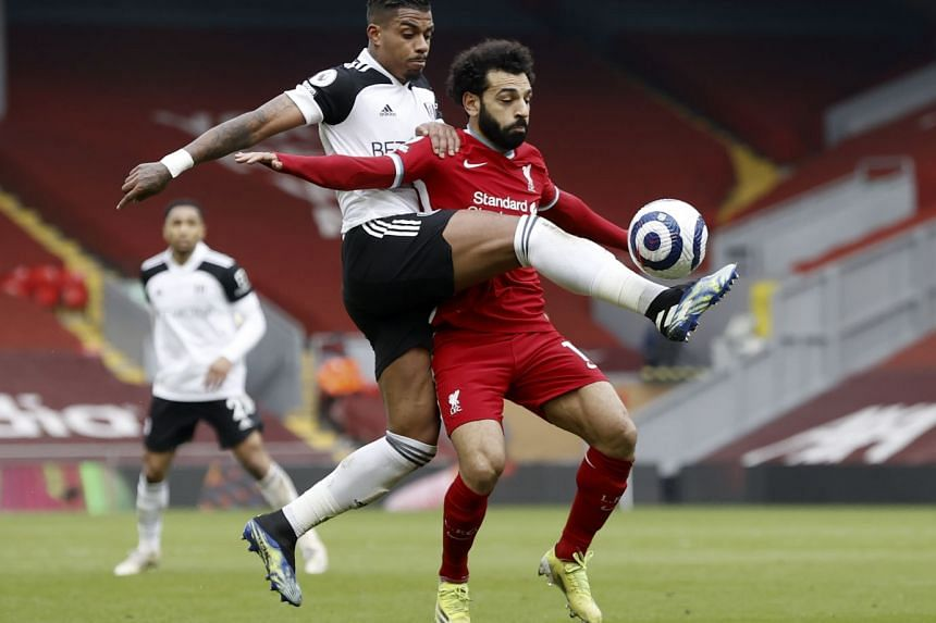 Fulham's Mario Lemina (left) in action against Liverpool's Mohamed Salah on March 7, 2021.