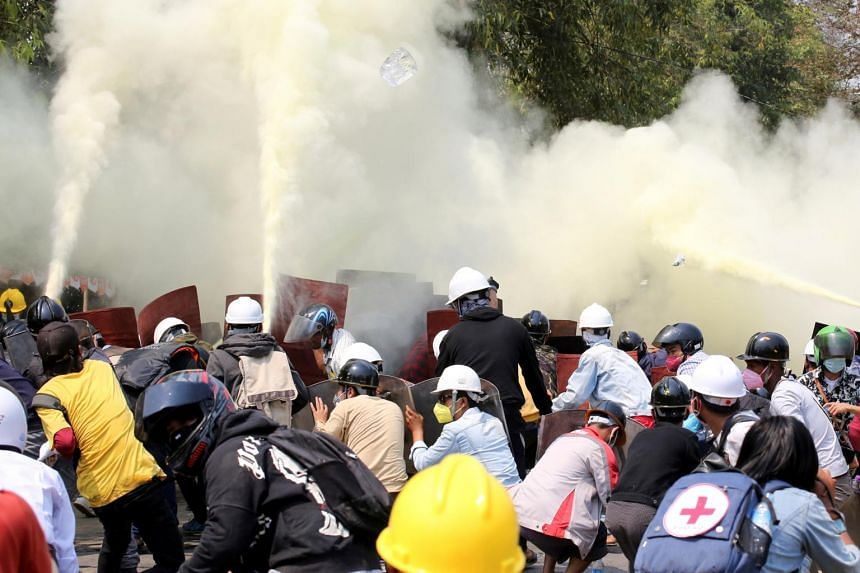 Tear gas and fire extinguisher gas float around demonstrators during a protest against the military coup in Naypyitaw, Myanmar, on March 8, 2021.
