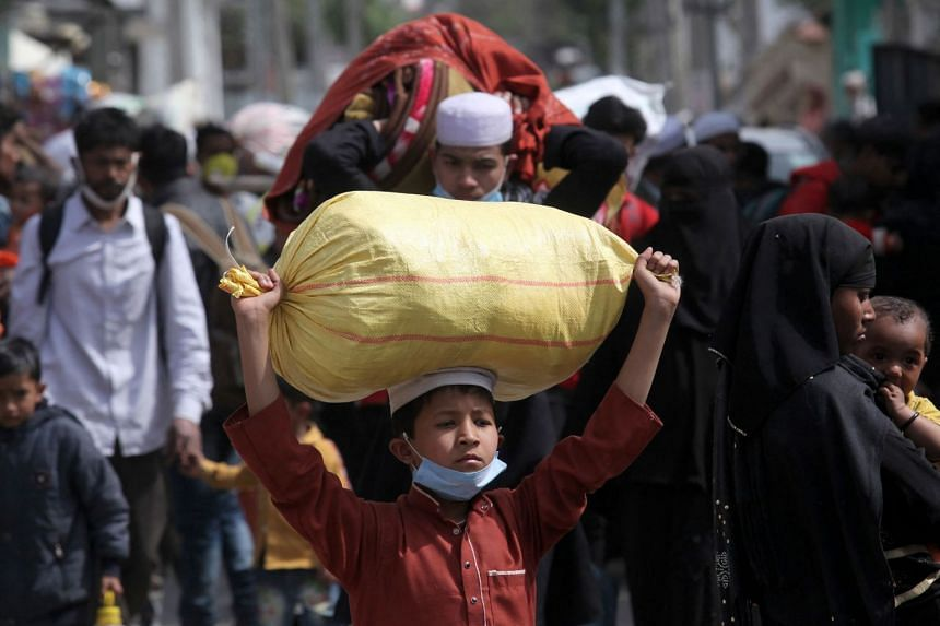 Rohingya refugees carry their belongings as they leave a refugee camp in Jammu, India, on March 7, 2021.