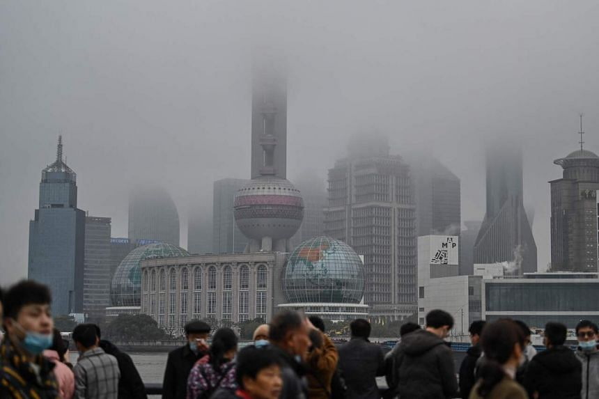 <p>People visit the Bund promenade in front of the Lujiazui financial district along the Huangpu river in Shanghai on March 7, 2021. (Photo by Hector RETAMAL / AFP)</p>