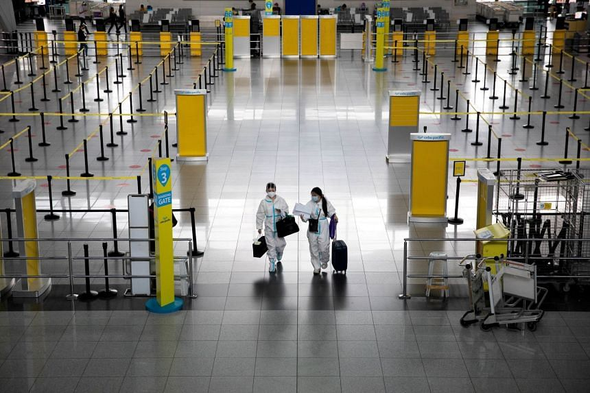 Passengers wearing hazmat suits walk inside Ninoy Aquino International Airport in the Philippines in January 2021.