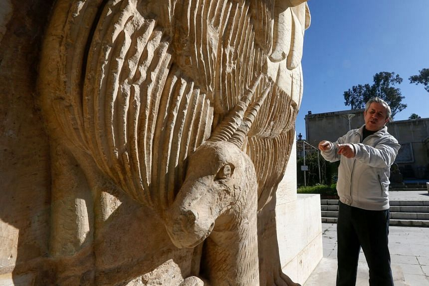 Syrian former antiquities chief Maamoun Abdulkarim outside Damascus Museum in front of a high relief sculpture on Feb 10, 2021.