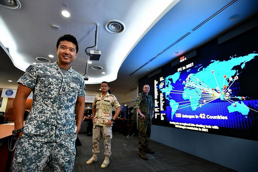 (From left) Lieutenant-Colonel Lester Yong, head of the Information Fusion Centre, with Lieutenant Sok Sal of Cambodia and Lieutenant Commander Christian Hegering of Germany at the centre at Changi Naval Base yesterday.