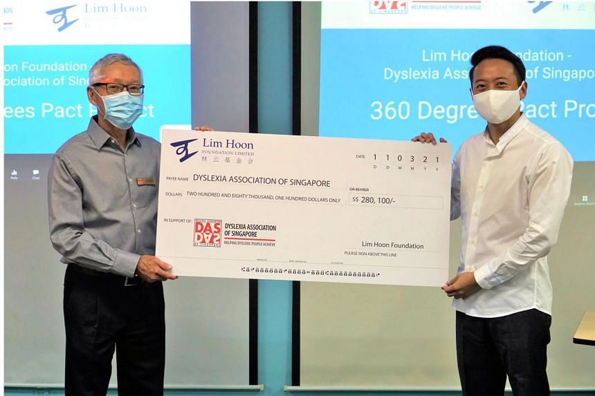 Mr Andy Lim (right), director of Lim Hoon Foundation, presenting the cheque to Mr Eric Lee, president of Dyslexia Association of Singapore.