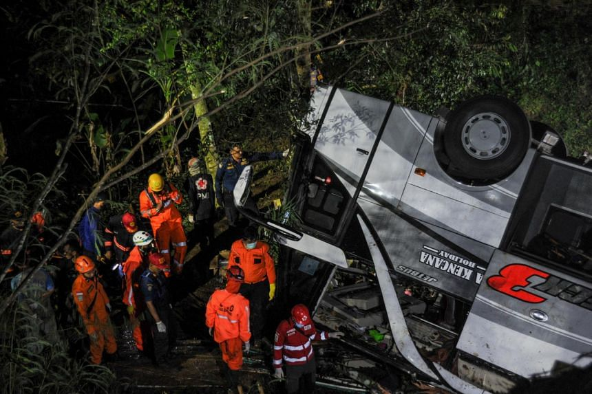 Rescue personnel work at the crash site after a bus fell into a ravine in Sumedang, West Java Province, on March 10, 2021.