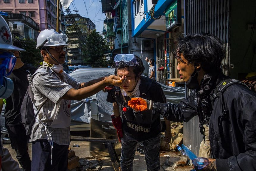 Volunteer medics help protesters wash their faces after security forces used tear gas to disperse people demonstrating against the military coup in Yangon, on March 9, 2021.
