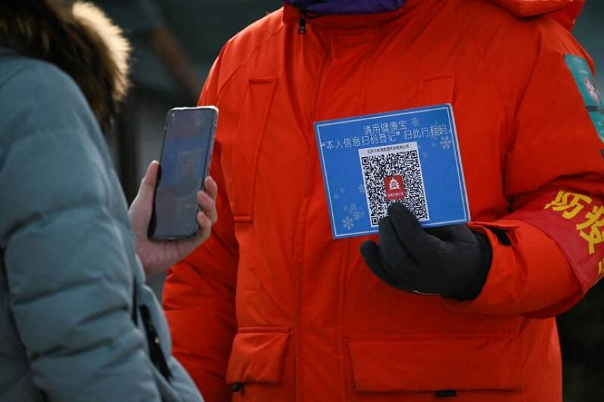 A woman using her mobile phone to scan a QR code for health registration before entering an outdoor ice rink in Beijing.