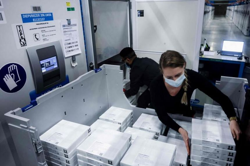 Employees put Pfizer-BioNTech Covid-19 vaccines into refrigeration at the company's factory in Puurs, on Feb 22, 2021.