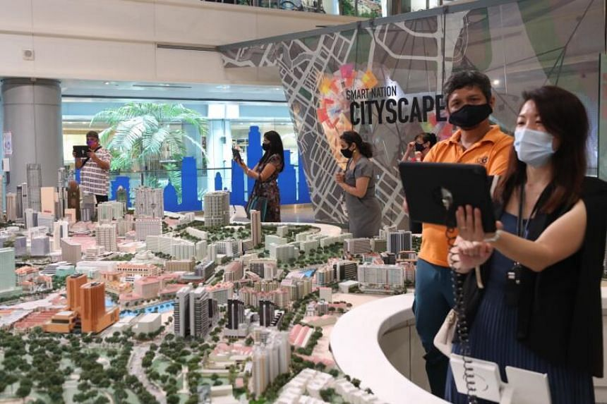 Smart Nation ambassadors using augmented reality technology to view a model of Singapore's city area at The URA Centre on March 11, 2021.