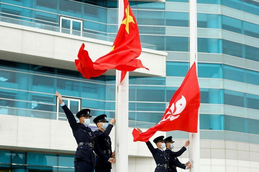 Police officers gesture at a China and Hong Kong flag-raising ceremony at Golden Bauhinia Square in Hong Kong, March 11, 2021.