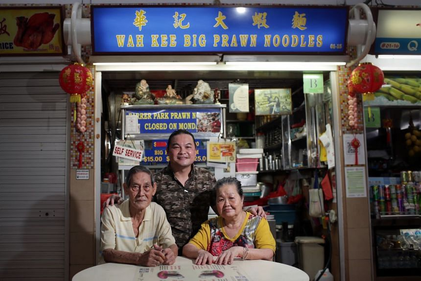 Mr Lau Fook Wah (left), Madam Tham Lay Mon and their son Kevin Lau at Wah Kee Big Prawn Noodles stall at Pek Kio Market and Food Centre, on March 8, 2021.