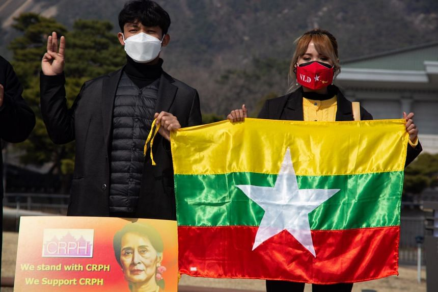 Myanmar nationals living in South Korea flash the three-finger salute during a protest against the Myanmar military coup in Seoul, on March 10, 2021.