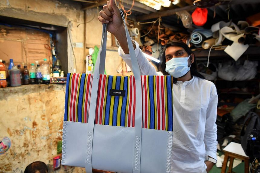 Founder of 'Chamar Studio' Sudheer Rajbhar shows his bags made from recycled rubber at a workshop inside Dharavi slum, in Mumbai, on Feb 2, 2021.