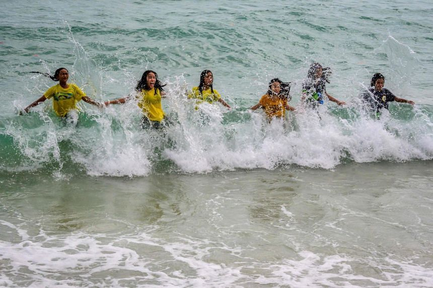 Children play in the waves on a beach in Koh Samui, on Jan 17, 2021.