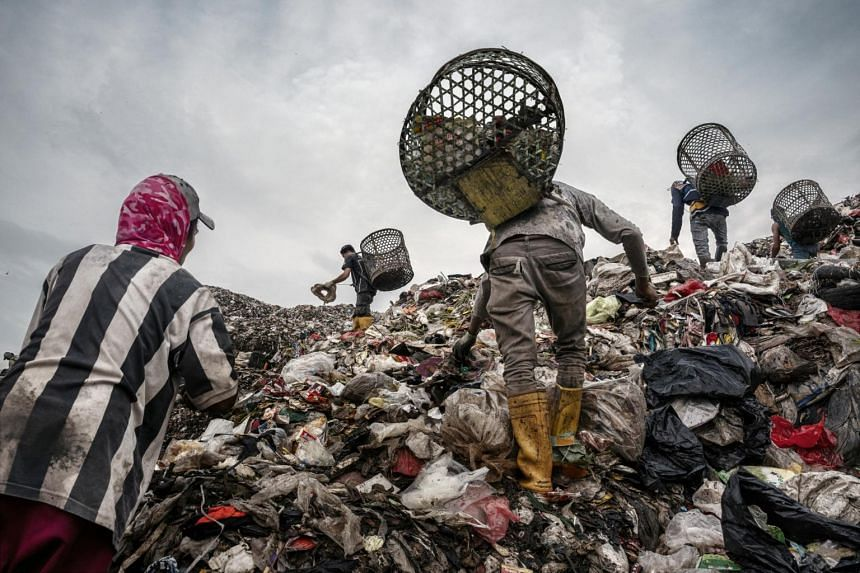 In a photo taken on Feb 28, 2020, trash pickers search for recyclable plastic and other items of value at a landfill in Bantar Gebang, Indonesia.
