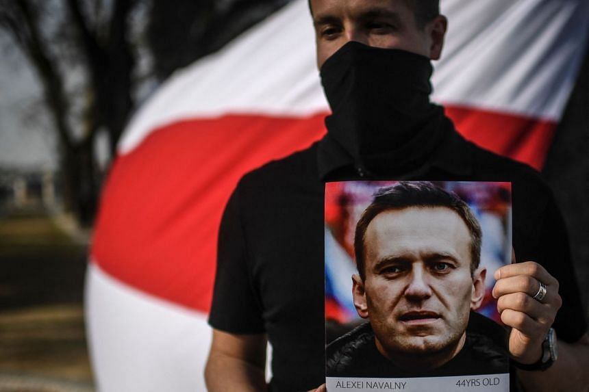 A man holds a portrait of Russian opposition leader Alexei Navalny during a demonstration in solidarity with political prisoners on March 6, 2021 in Lisbon.