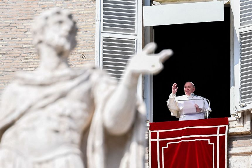 Pope Francis waves during prayers from a window of the apostolic palace overlooking St Peter's square in the Vatican City in February 2021.