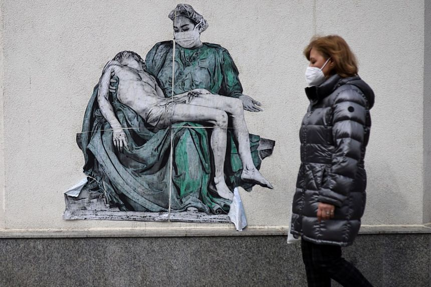 A woman walks past a poster - illustrating a medic in a replica of Michelangelo's Pieta - on a wall near a vaccination centre in Sofia, Bulgaria.