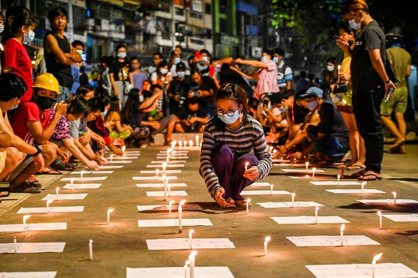 A protester places candles on the ground during a night-time demonstration against the military coup in Yangon on March 13, 2021.