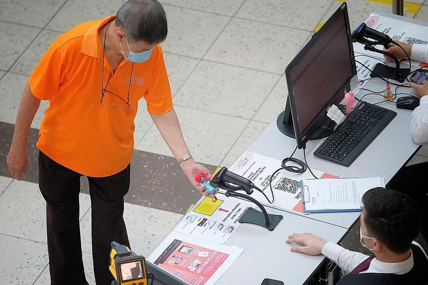 A visitor scanning a TraceTogether token before entering HarbourFront Centre last month. TraceTogether, which identifies people in close contact with a Covid-19 patient via Bluetooth, came under the spotlight earlier this year when it was revealed th
