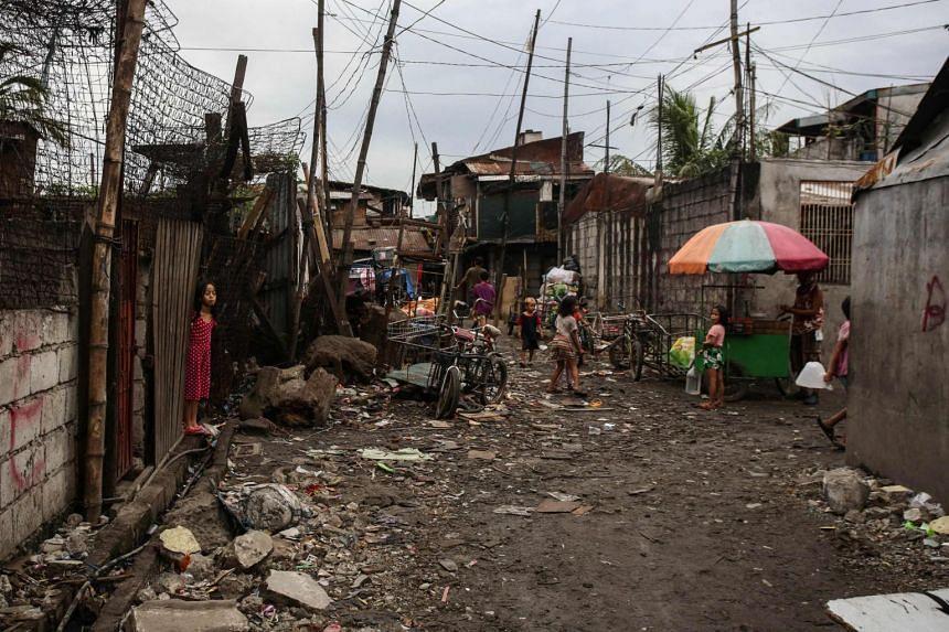 Children play along an alley at an informal settlers area in Malabon City, suburban Manila, on Feb 10, 2021.