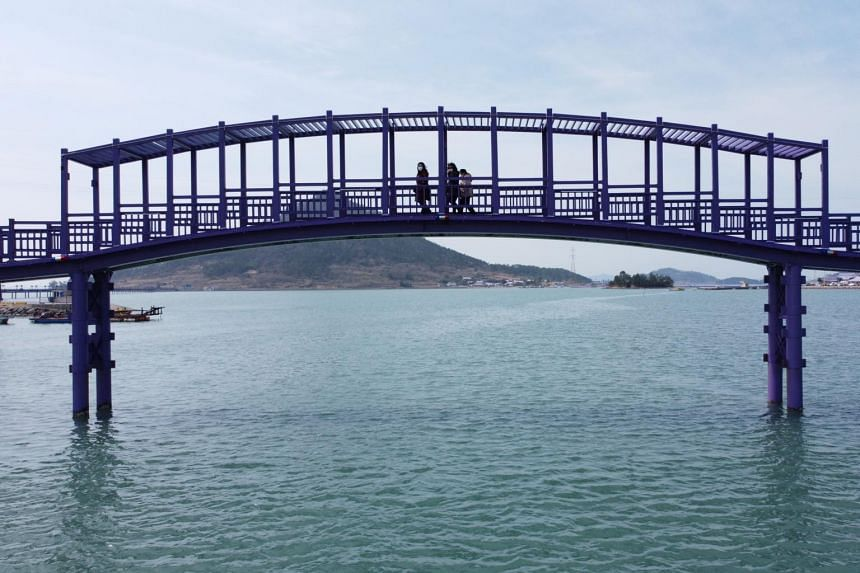 Visitors can walk three purple footbridges connecting the two islands to the larger one near it.