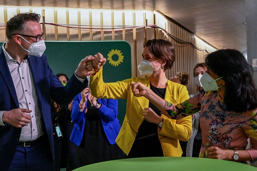 (From left) The Greens regional parliamentary group leader Andreas Schwarz, Sandra Detzer and Muhterem Aras react as exit poll results are published at the state parliament in Stuttgart, on March 14, 2021.