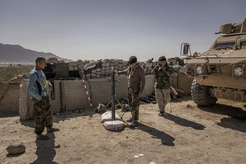 Afghan army commandos fire a mortar from an outpost near the front line with the Taleban in Panjwai on March 7, 2021.