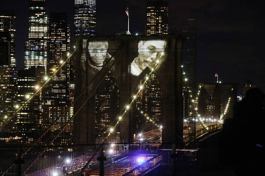 Faces of victims of Covid-19 are projected onto the Brooklyn Bridge during a memorial service in New York City, on March 14, 2021.
