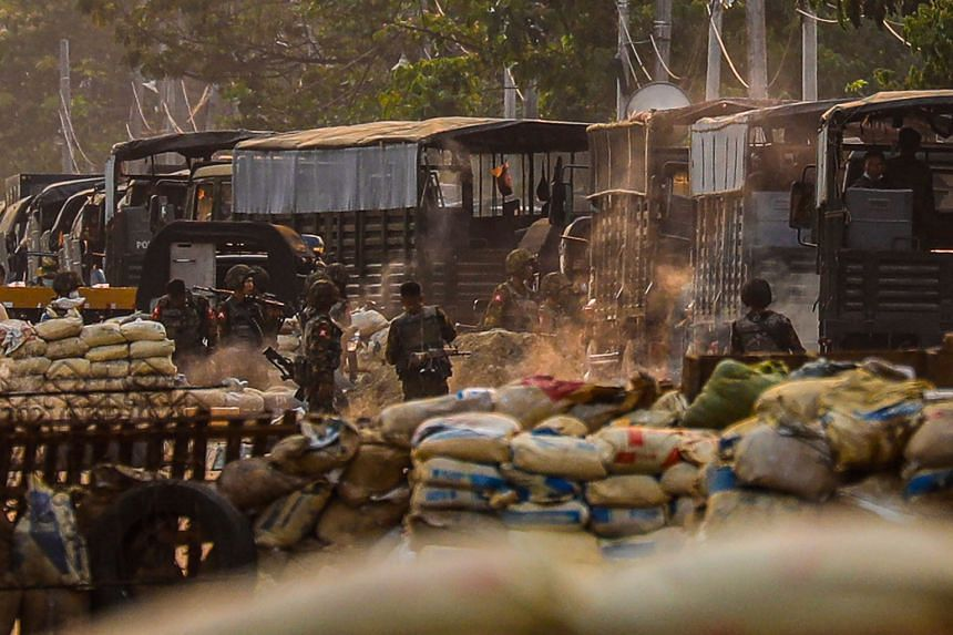 Soldiers are seen near makeshift barricades set up by protesters in Hlaingthaya township in Yangon, on March 14, 2021.