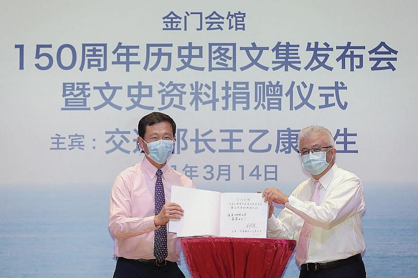 Transport Minister Ong Ye Kung and Kim Mui Hoey Kuan president Thomas Chua unveiling the new book, Our Voyage Through Time, at an event on Sunday to celebrate the Chinese clan association's 150th anniversary.