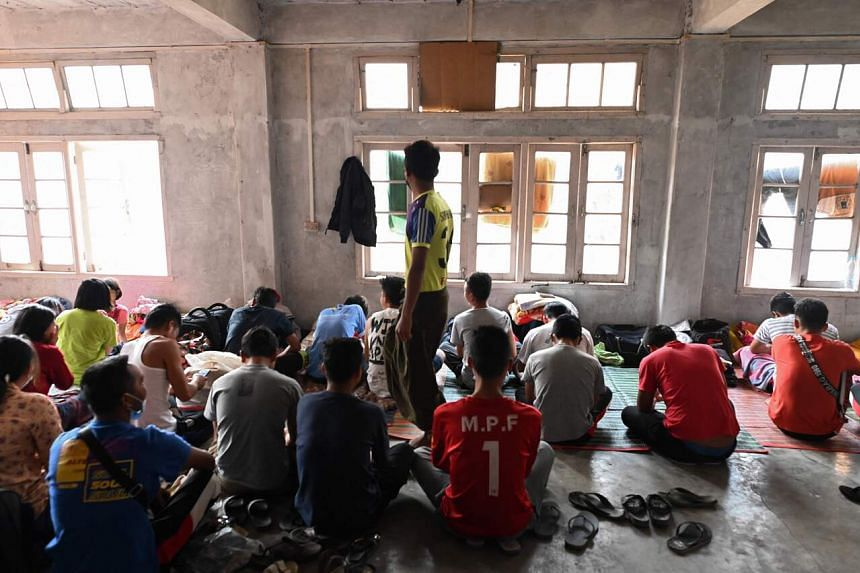 Policemen who fled Myanmar and crossed illegally to India sit in a temporary shelter at an undisclosed location in India's northeastern state of Mizoram, on March 13, 2021.