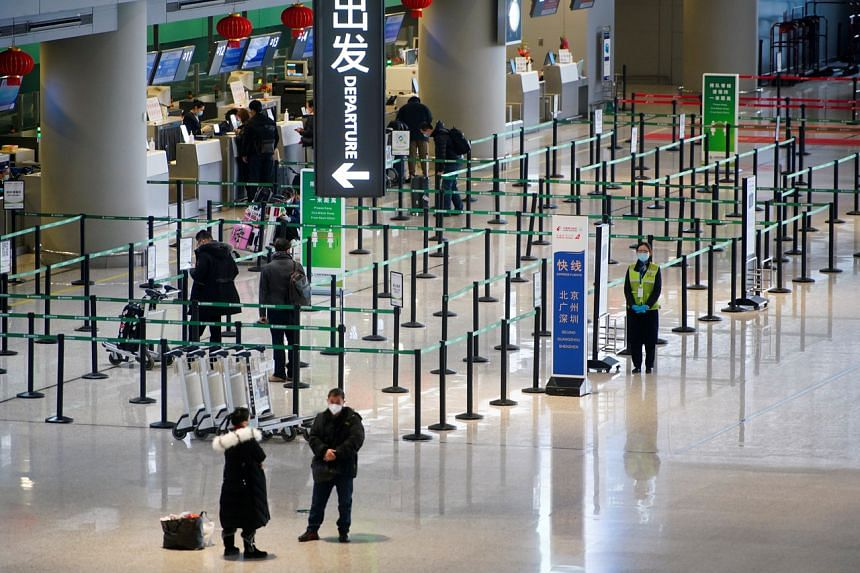 Travellers wait at check-in counters of Shanghai Hongqiao International Airport, in China, on Jan 28, 2021.