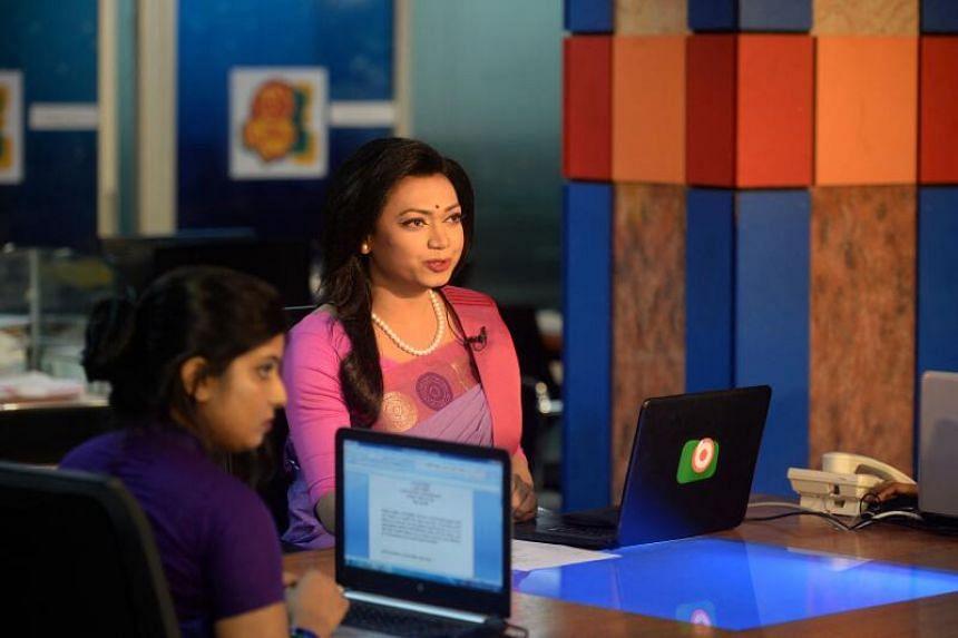 Tashnuva Anan Shishir (right) presents the news on television at a news studio in Dhaka, on March 8, 2021.