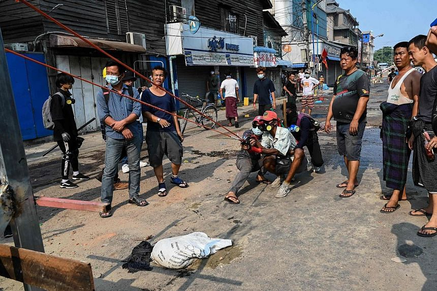 Protesters testing a large slingshot weapon in Yangon yesterday, as security forces continued a crackdown on demonstrations against the military coup. Social media footage showed protesters confronting security forces over a sandbag barricade in the