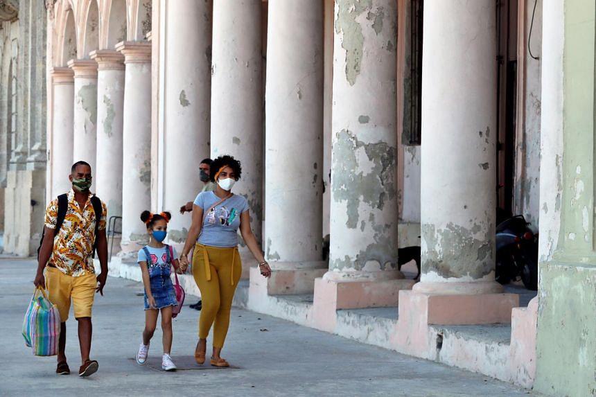Groups of people wearing a mask walk down a street in Havana, Cuba, on March 11, 2021.