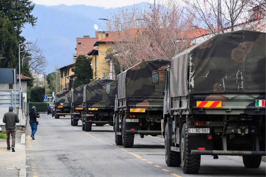 Italian army trucks transporting coffins of victims of the coronavirus cross the city of Bergamo, Lombardy, on March 26, 2020.