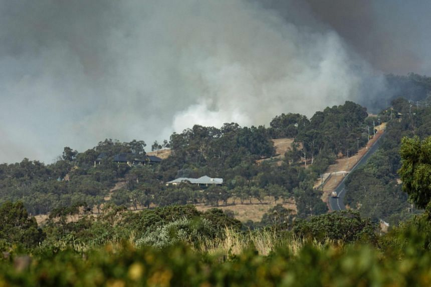 Smoke rises behind a hill as a house is threatened by fires in the suburb of Baskerville near Perth on Feb 3, 2021.