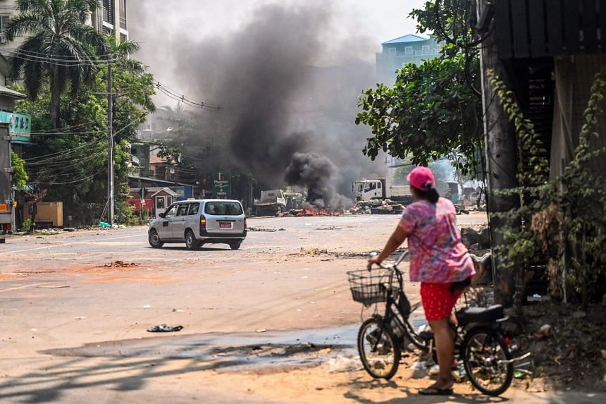 A cyclist watches as soldiers set barricades on fire in attempt to clear the road of obstructions in Yangon on March 19, 2021.