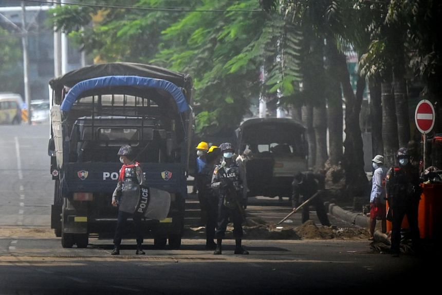 Police stand guard on a road in Yangon, on March 19, 2021.