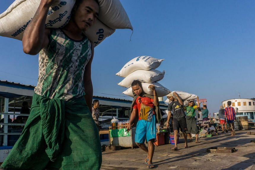 Labourers unload sacks of rice from a ship at a jetty in Yangon, on Feb 3, 2021.