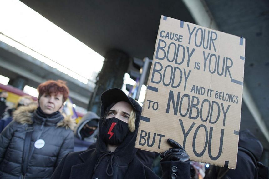 Demonstrators take part in a protest against Poland's near-total ban on abortion in Warsaw, on March 8, 2021.