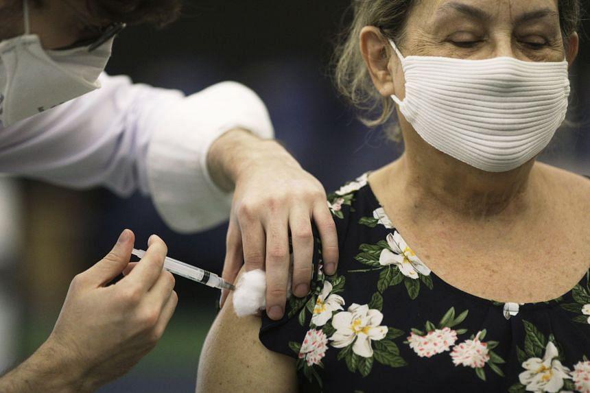 A health worker applies Sinovac's CoronaVac Covid-19 vaccine to an elderly lady at Rio de Janeiro's planetarium, on March 18, 2021.