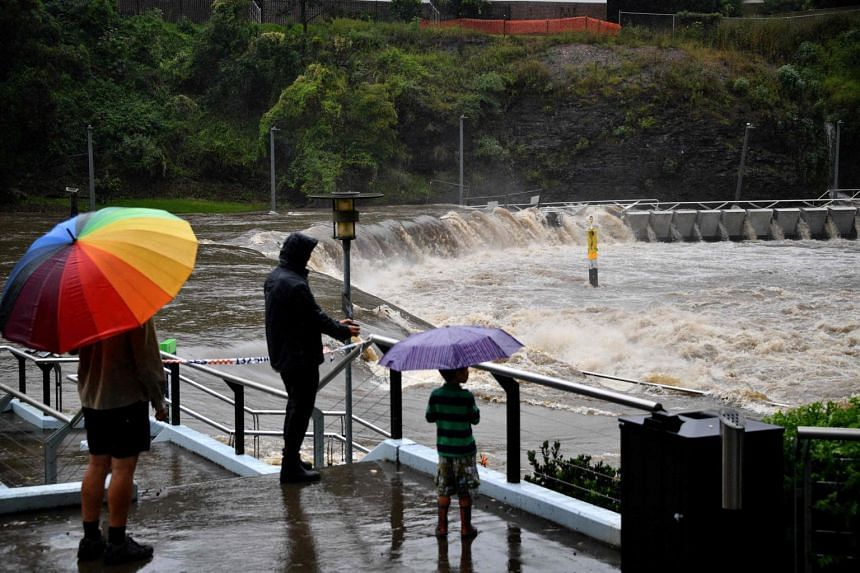 Residents watch the overflowing Parramatta river during heavy rain in Sydney, on March 20, 2021.