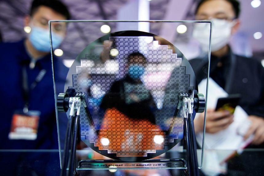 Visitors look at a display of a semiconductor device at Semicon China, a trade fair for semiconductor technology, in Shanghai, China, on March 17, 2021.