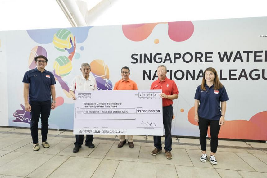 Tan Eng Liang (in white) presents a cheque at the launch of the Singapore Olympic Foundation-Tan Family Water Polo Fund at Our Tampines Hub on March 21, 2021.