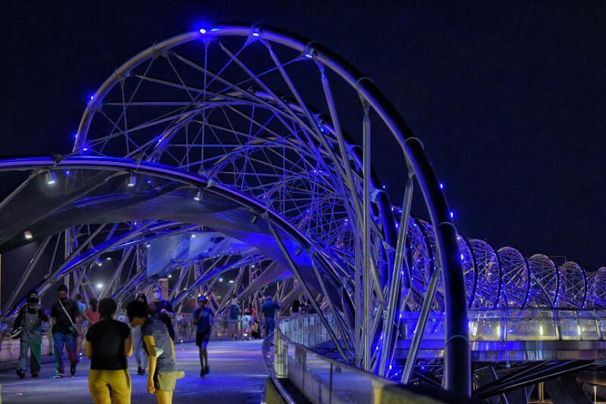 The Helix Bridge is lit in blue on March 21, 2021.